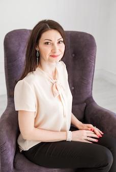 Modisches brünettes mädchen in einer hellen bluse sitzt auf einem stuhl, posiert und schaut in die kamera.