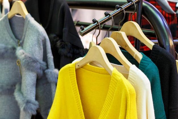 Modisches ceylon-gelb und andere farbwollgestrickte strickjacken, die an den aufhängern im speicher, nahaufnahme hängen
