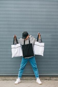 Modisches foto eines jungen mannes in streetwear mit öko-taschen in seinen händen.