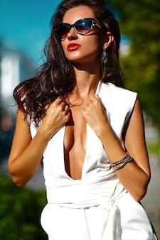 Modisches frauenmädchenmodell im weißen anzug in der sonnenbrille in der straße