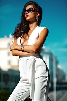 Modisches frauenmodell im weißen anzug in der sonnenbrille auf der straße