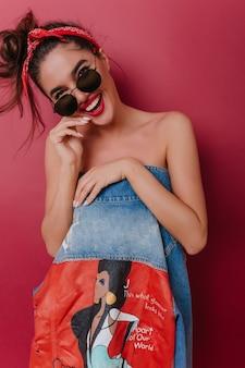 Modisches gebräuntes mädchen mit aufrichtigem lächeln, das körper mit jeansjacke bedeckt