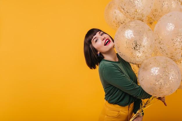 Modisches geburtstagskind, das mit interessiertem gesichtsausdruck aufwirft. elegante frau isoliert mit funkelnden heliumballons.