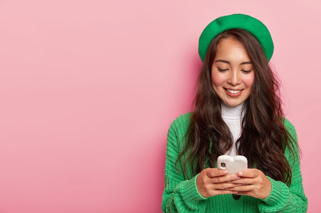 Modisches hübsches asiatisches mädchen hält handy, gekleidet in grüne kleidung, surft im internet auf modernem handy, sendet sms