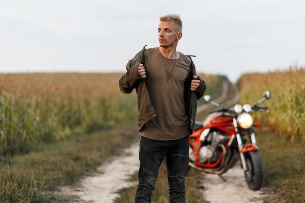 Modisches hübsches junges modell eines mannes in einer khakijacke mit einem t-shirt nahe einem motorrad wirft in einem maisfeld auf