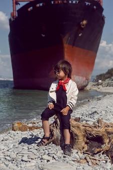 Modisches jungenkind mit langen haaren sitzt auf einem baumstamm neben einem großen schiff, das in der nähe von novorossiysk auf grund lief