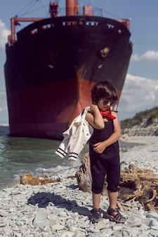 Modisches jungenkind mit langen haaren steht auf einem baumstamm neben einem großen schiff, das in der nähe von novorossiysk auf grund lief