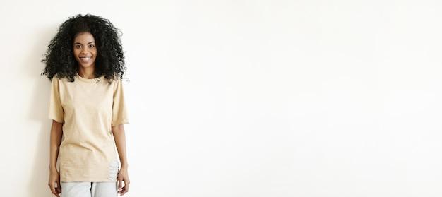 Modisches junges dunkelhäutiges weibliches modell mit hübschem lächeln, das lokal gegen weiße wand aufwirft