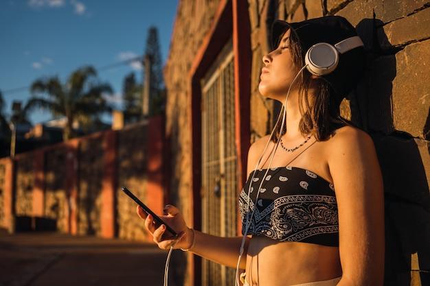 Modisches junges mädchen, das musik im freien genießt