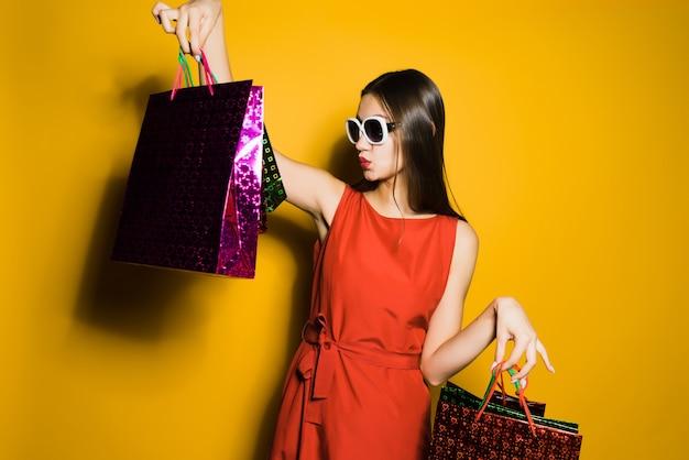 Modisches junges mädchen shopaholic mit sonnenbrille ging an einem schwarzen freitag einkaufen