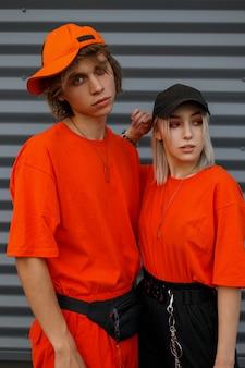 Modisches junges schönes paar mit kappen in leuchtend orange modischen kleidern nahe der metallgrauen wand. mode mann und frau