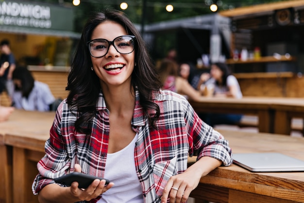 Modisches kaukasisches mädchen mit smartphone, das im café mit lächeln aufwirft. wunderschöne studentin, die im restaurant im freien mit laptop sitzt.