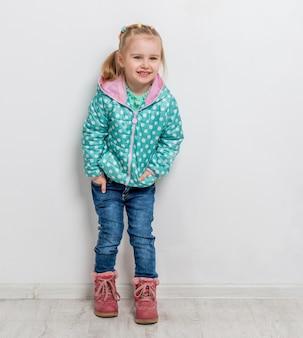 Modisches kleines mädchen in den jeans, in der jacke und in den stiefeln