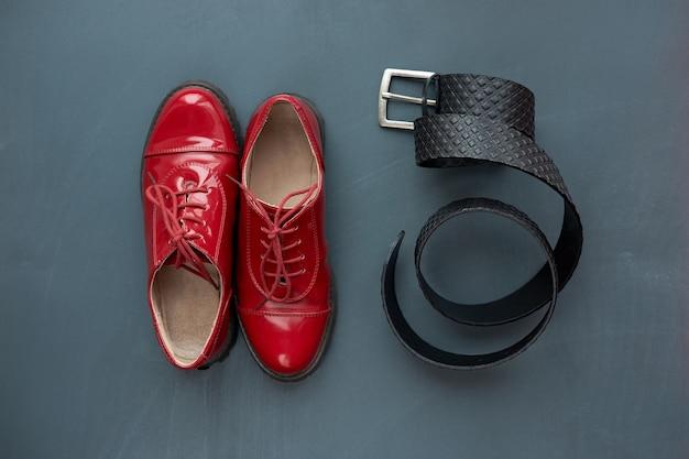 Modisches konzept. trendy rote lackschuhe und schwarzer ledergürtel für hosen auf grauem hintergrund. draufsicht.