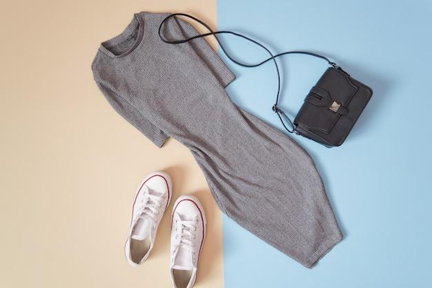 Modisches konzept. urbaner frauenstil. graues kleid, weiße turnschuhe und schwarze handtasche auf einem weichen blauen hintergrund, beige