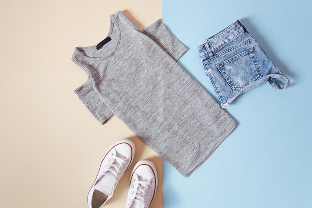 Modisches konzept. urbaner frauenstil. graues t-shirt, weiße turnschuhe und kurze jeanshose auf einem weichen blauen hintergrund