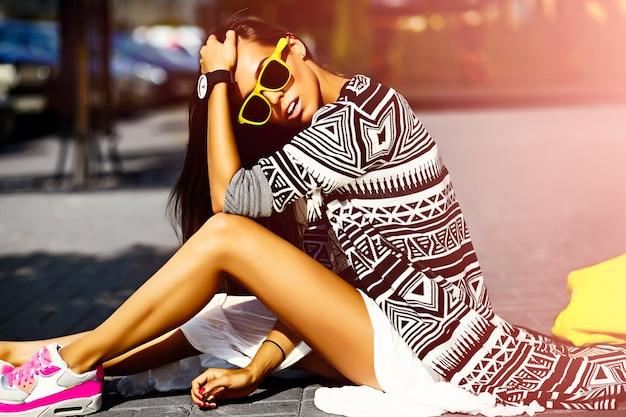 Modisches lustiges glamour stilvolles sexy lächelndes schönes junges frauenmodell in der hipster-sommerkleidung, die in der straße mit dem einkaufen der leuchtend gelben tasche sitzt