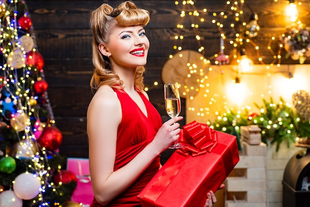 Modisches luxusmädchen, das neues jahr feiert. retro frau nahe dem weihnachtsbaum. lächelnde frau herein