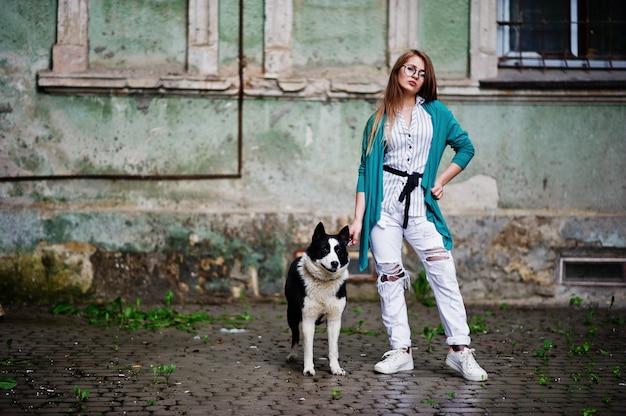 Modisches mädchen an den gläsern und an zerrissenen jeans mit russisch-europäischem hund laika (heiser) an einer leine, gegen straße der stadt