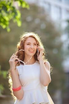 Modisches mädchen, das auf der stadtstraße geht und durch das telefon spricht