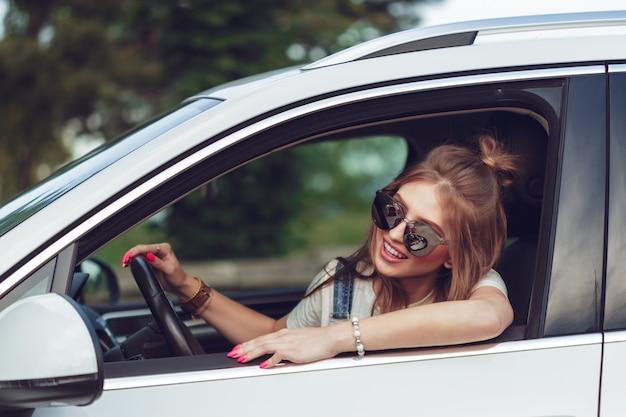 Modisches mädchen, das mit dem auto reist