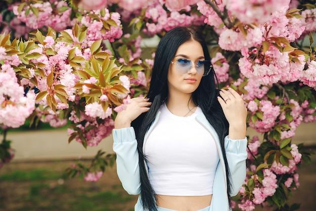 Modisches mädchen in der trendigen brille. frühlingstag. rosa blüten des kirschbaums. sexy schönes mädchen in modekleidung. garten mit blühenden großen kirschbäumen