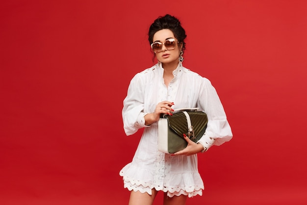 Modisches model-mädchen in einem weißen kleid und einer trendigen sonnenbrille posiert mit einer goldenen handtasche über rotem rücken...