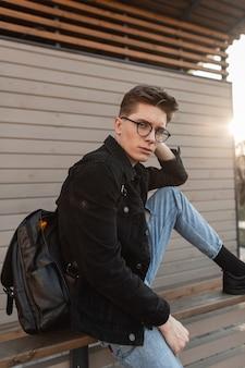 Modisches modell des jungen mannes mit frisur in stylischer jeans-freizeitkleidung in stylischer brille