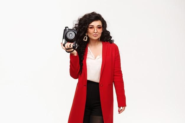 Modisches modell in rotem mantel, großen goldenen ohrringen und runder sonnenbrille, die mit alter kamera in ihrer hand aufwirft