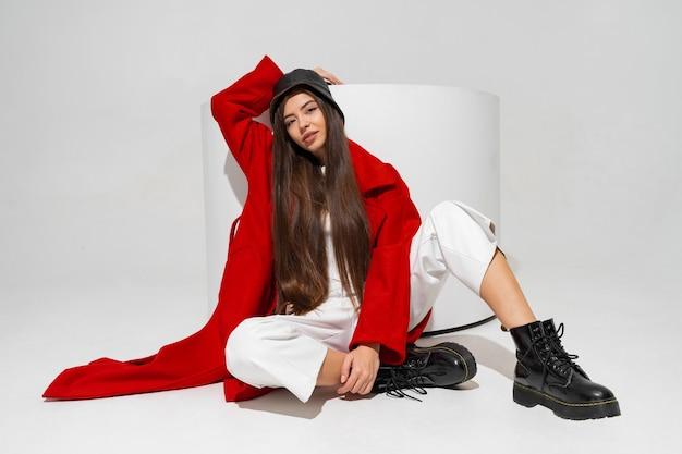 Modisches modell in stilvollem hut, rotem mantel und stiefeln posiert auf weißer wand im studio