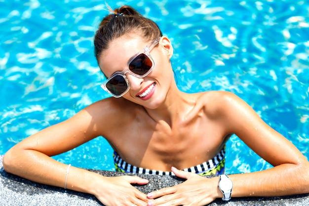 Modisches nahaufnahme-modeporträt der sexy gebräunten frau entspannte sich und schwamm am pool. trägt einen hellen bikini und eine sonnenbrille, lächelt und schaut
