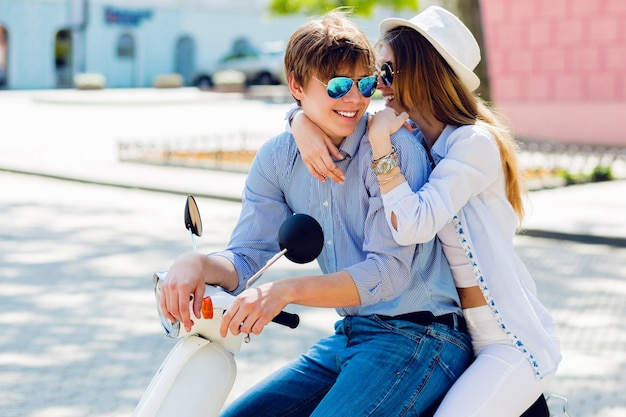 Modisches paar posiert auf der straße und sitzt auf einem roller