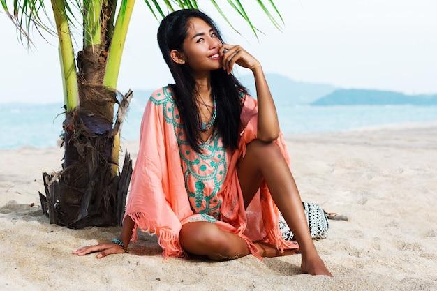 Modisches porträt der asiatischen frau, die auf dem tropischen strand aufwirft