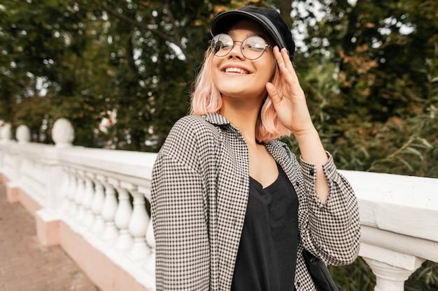 Modisches porträt eines schönen teenager-mädchenmodells in brille mit einem stilvollen karierten hemd und einem t-shirt geht im park spazieren