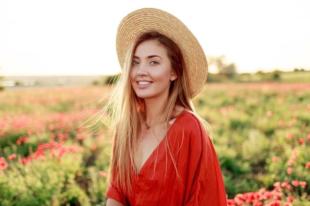Modisches porträt im freien der atemberaubenden blonden frau, die während des spaziergangs im erstaunlichen mohnfeld im warmen sommerabend aufwirft. tragen von strohhut, trendiger tasche und rotem kleid.