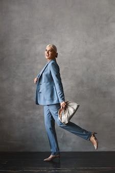 Modisches porträt in voller länge einer vorbildlichen frau mit blonden haaren im trendigen anzug und mit stilvollem geldbeutel, der in die kamera schaut und drinnen posiert