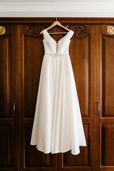 Modisches schönes klassisches spitzenseidenhochzeitskleid, das auf kleiderbügel im hotelholzzimmer hängt. morgenvorbereitung hochzeitskonzept. vintage brautkleid.