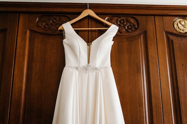 Modisches schönes klassisches spitzenseidenhochzeitskleid, das auf kleiderbügel im hotelholzzimmer hängt. morgenvorbereitung hochzeitskonzept.
