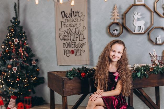 Modisches schönes mädchen im kleid zu hause nahe silvester und weihnachtsdekorationen und bunten lichtern