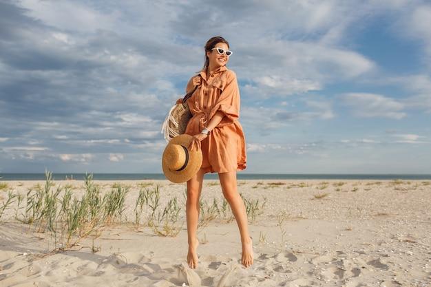 Modisches sommerbild der schönen brünettenfrau im trendigen leinenkleid, das strohsack hält. hübsches schlankes mädchen, das wochenenden in der nähe des ozeans genießt.