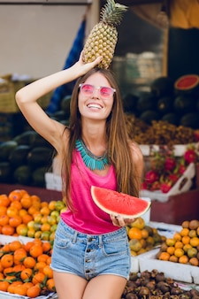 Modisches sommermädchen, das auf markt auf tropischem fruchtmarkt genießt. sie hält ananas auf dem kopf und eine scheibe wassermelone in der hand dahinter