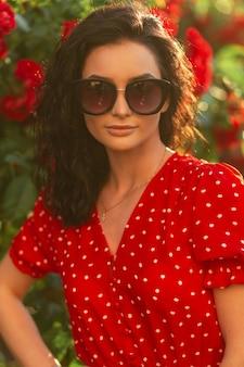Modisches sommerporträt eines schönen eleganten lockigen mädchens mit vintage-mode-sonnenbrille in einem roten retro-kleid steht im park in der nähe eines busches mit rosen