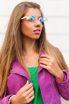 Modisches stilvolles mädchen in der sonnenbrille und in einer hellen rosa jacke auf einem weiß