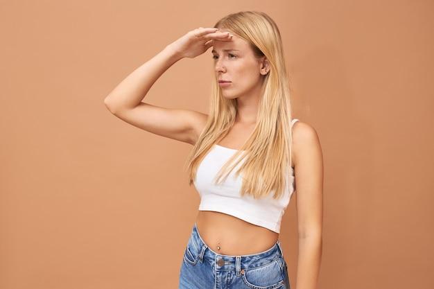 Modisches süßes junges mädchen mit blonden haaren trägt jeans und weißes oberteil
