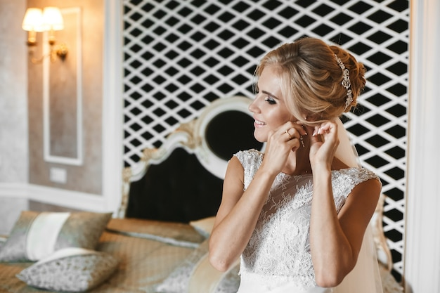 Modisches und elegantes blondes modellmädchen mit stilvoller hochzeitsfrisur, im spitzenkleid, setzt ihren ohrring auf und posiert im innenraum