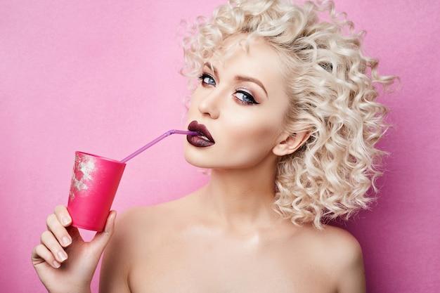 Modisches und schönes blondes modellmädchen mit blauen augen und mit professionellem hellem make-up, trinkt durch einen strohhalm von einem rosa glas und posiert im studio am rosa hintergrund