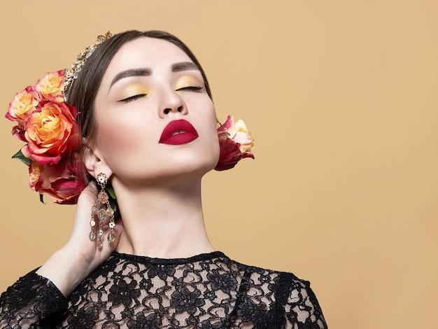 Modisches und schönes model posiert mit einem strauß roter rosen.