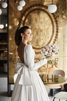 Modisches und sexy brünettes modellmädchen mit hellem make-up und mit hochzeitsfrisur, in einem trendigen beigen kleid mit nacktem rücken, das mit dem blumenstrauß in ihrer hand im luxusinnenraum posiert