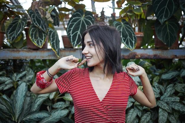 Modisches, verspieltes 20-jähriges mädchen mit bob-haaren, gestreiftem kleid und lappen am handgelenk, beißendem finger und seitlichem blick mit mysteriösem lächeln, versteckt sich im grünen vor ihrem freund