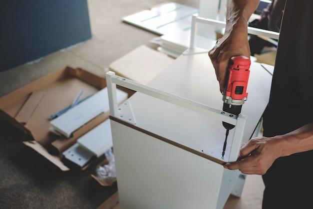 Möbel zu hause zusammenbauen. umzug in ein neues haus oder ein diy-konzept. handwerker, der einen kabellosen schraubendreher verwendet, um das gehäuse zu installieren.